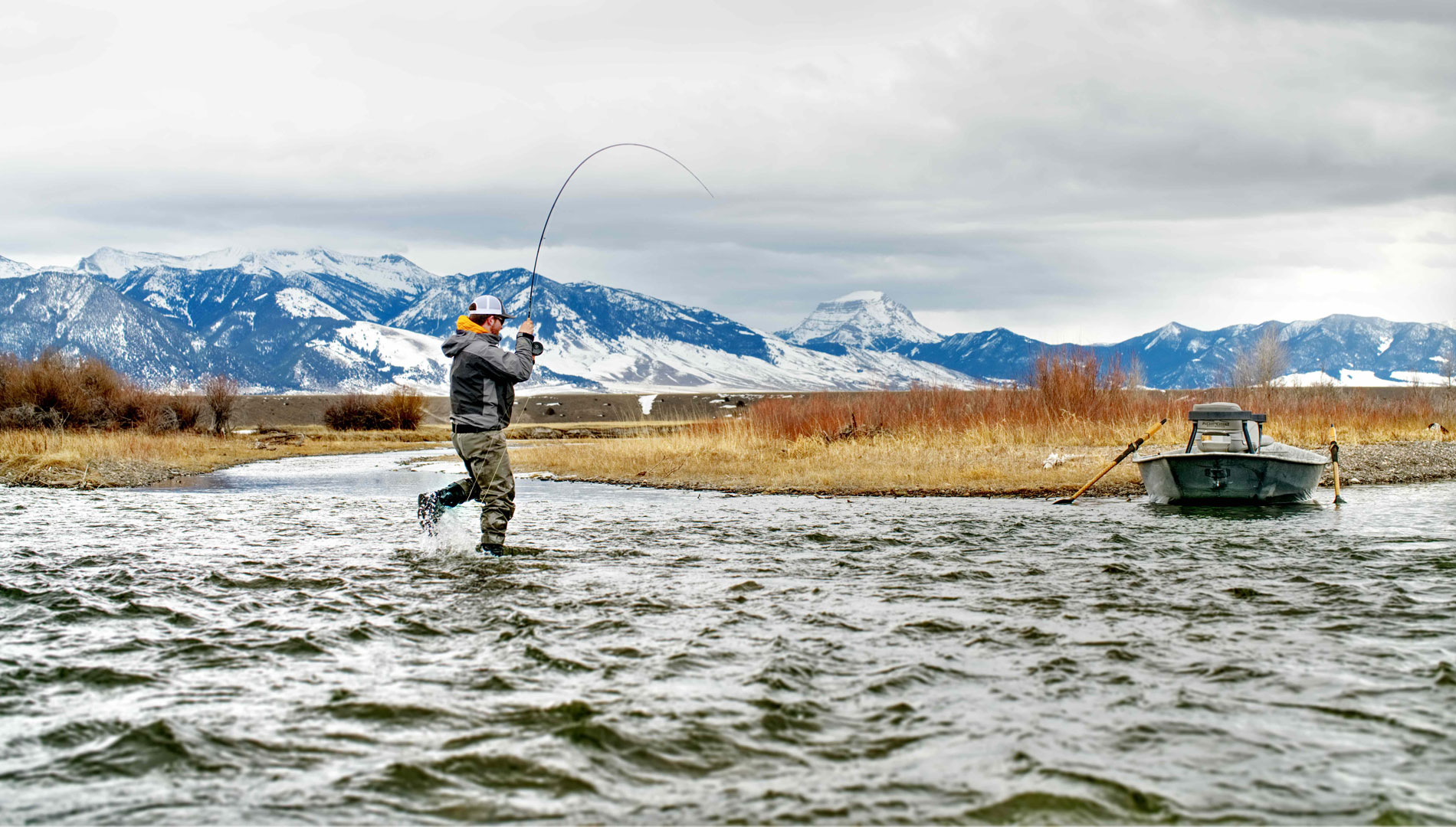 fly fisherman has a fish on along madison river