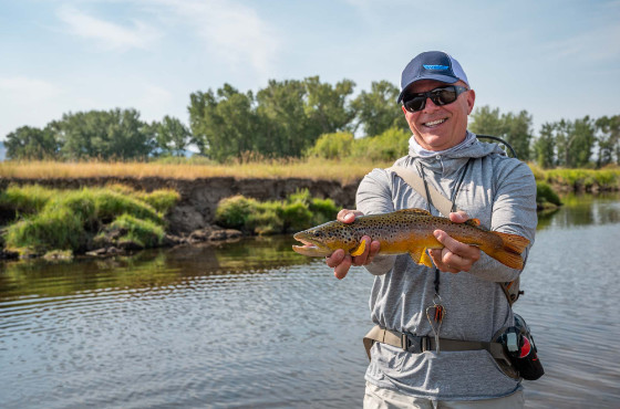 Angler with brown trout on small stream in Montana